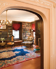 Off the living room, the walnut paneled library incorporates built-in window seats and shelving holding books in Russian and English. The oriental rug and tapestry-upholstered bergere are typical of the furnishings throughout the house.
